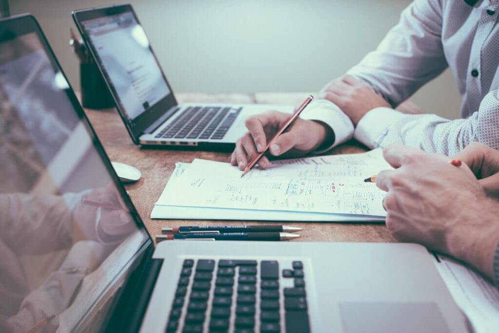 Hvordan finder man en virksomheds værdi? Udregner værdi, papir, computere, blyant.